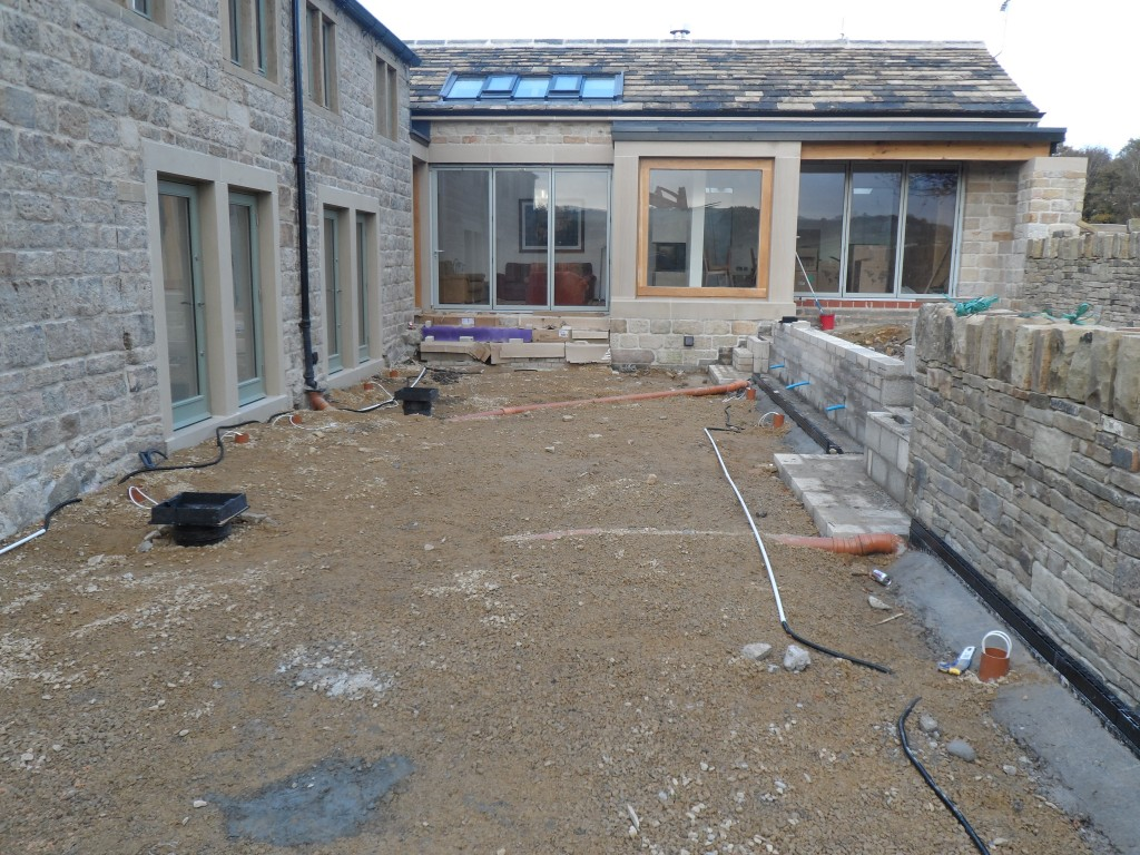 There are a number of uplighters around the perimeter of both the lower and upper terraces.  The wiring has to be put in place before the flagstones are laid.  We know the position of the lights so that we can drill the holes after the flagstones have been laid.