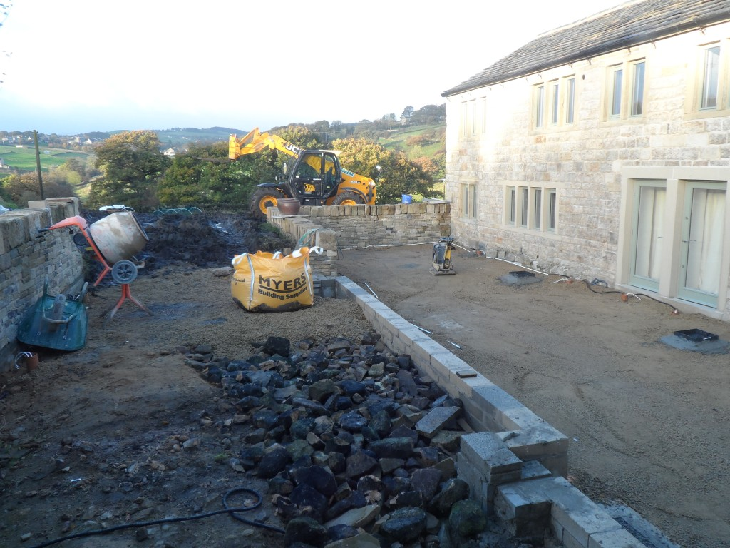 The upper terrace still has to be levelled, but we are taking the opportunity to get rid of some of the waste stone behind the retaining wall.