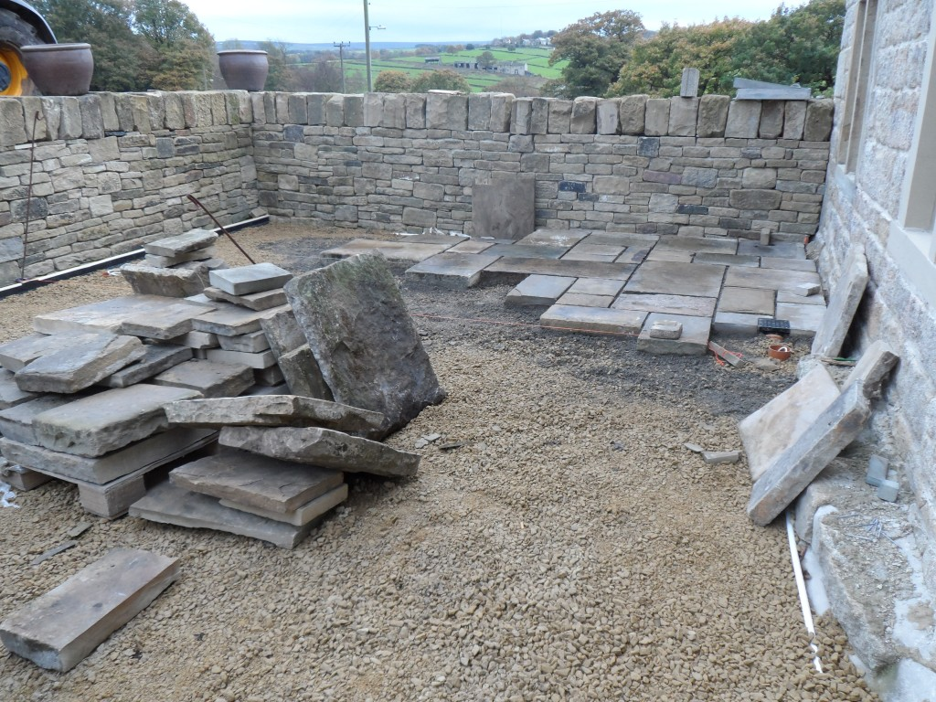 The thicker of the flagstones are probably on the weight limit for two men to carry - you certainly don't want to have to move them far.  Fortunately, we have managed to move the pallets into the sunken garden using the telehandler.