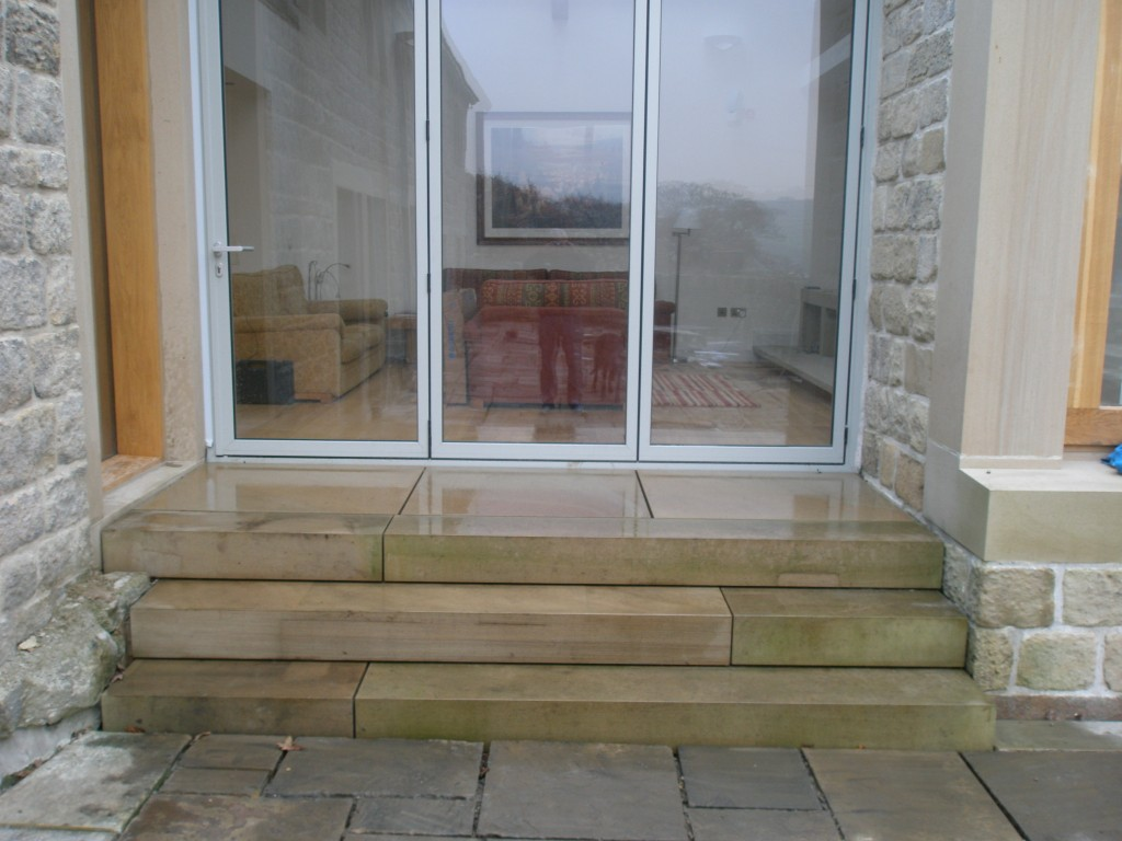 "These steps still need to be pointed, but the steps are pretty much complete.  They also need to be pressure washed to get the ""green"" of them - they have been covered for the past few weeks to protect them. Once cleaned, the steps will match the new slabs installed in front of the doors."
