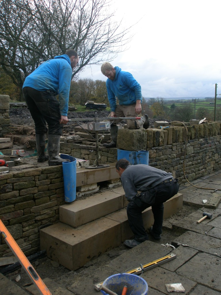 Once the step is roughly in position (but still resting on the slabs of insulation), the stone step is lifted up (the sides are protected by some thin blue foam) and the insulation removed (very quickly).  If it all works out properly, the stone step ends up in the right spot!