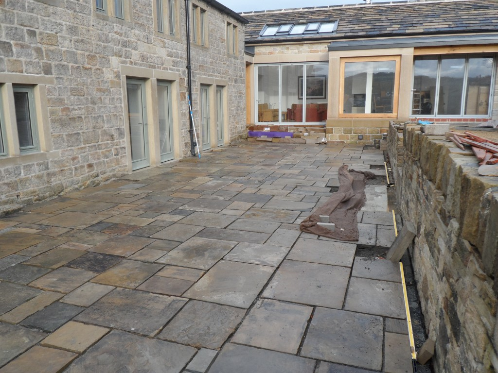 The flagstones gently slop away from the house and any rainwater is connected by a drain that runs along the back of this area (you can just see the slot (protected by a yellow strip) to camera right).  There are a couple of flagstones that are propped up against the wall.  These need to be drilled to take the uplighters that will be installed later.