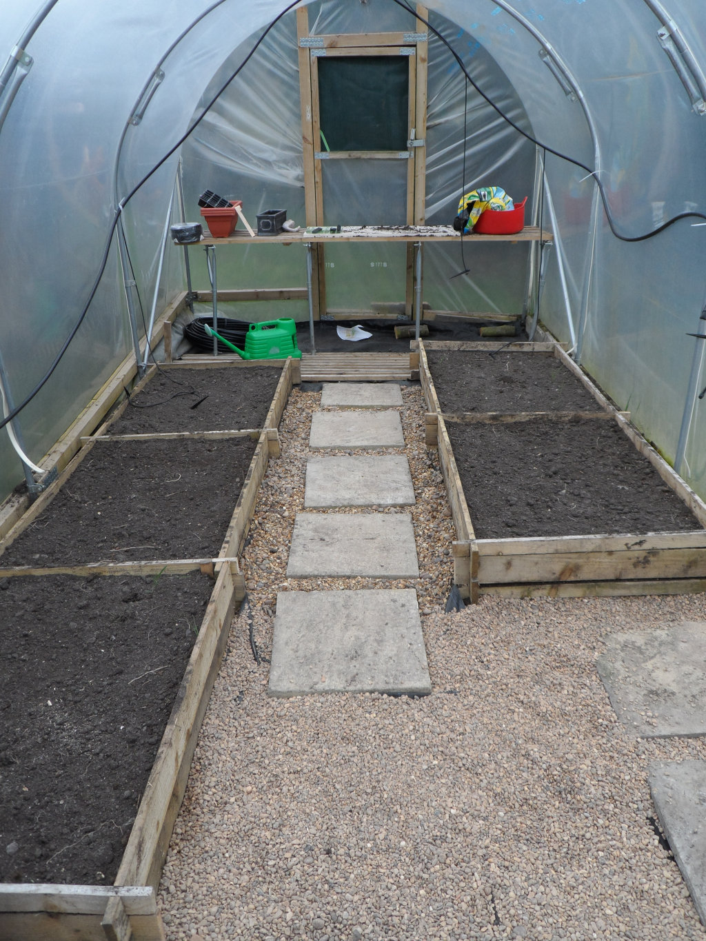 Rather than 4 wide beds, there are now 5 narrower beds.  This leaves room in the middle for a path and means that you can reach the back of the beds without having to stand on them.  The workbench now runs across the polytunnel rather than down all of one side.