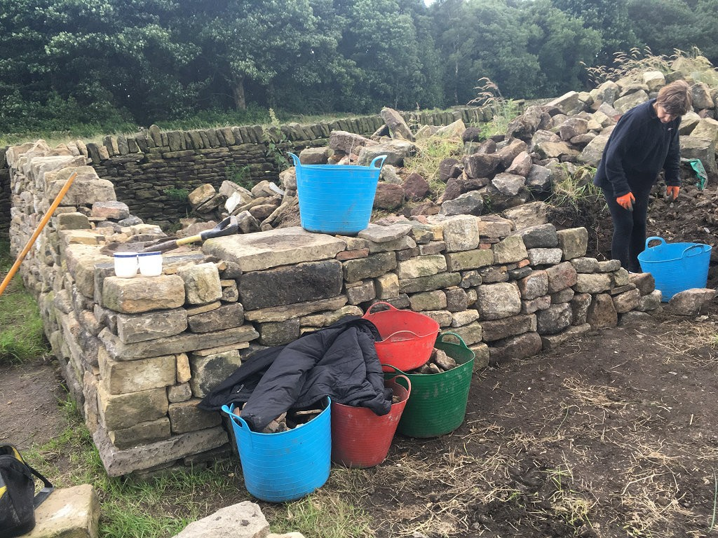 "The buckets are full of smaller stones that are used to ""pack out"" the middle of the wall.  You'll be amazed at how much stone can be used up doing this and how stable the smaller stones make the whole structure.  While I get to put the bigger stones in place, Jo gets to work fill the centre of the wall behind me."