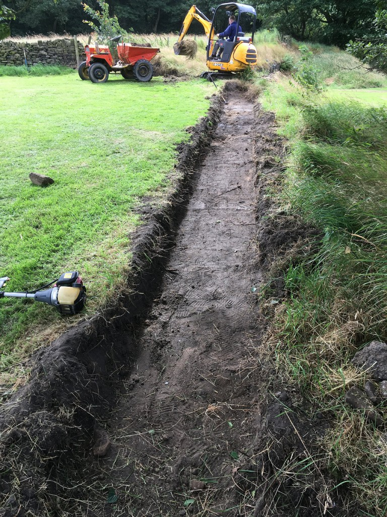 We have always dug all of the footings for our dry stone walls by hand - not this time!  We just happened to have access to a machine (and a man who knows how to drive it).  It only took a couple of hours to do what might have taken a couple of days by hand.  We used our old trusty dumper to move the soil elsewhere.  It is probably a good 30-40m run.
