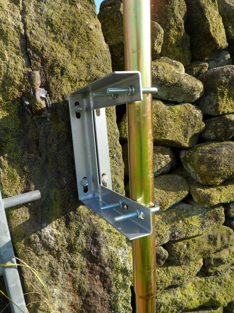 I drilled some over-sized holes into this stone gate post.  I then used anchor set to fix some threaded bar into the holes (actually, these were bolts with the heads cut off).  I then used some nuts and washers to adjust the pole so that it was fixed in the upright position. Shame the camera wasn't level!